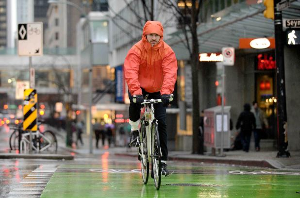 A cyclist pedals in the rain on the Dunsmuir bike path.