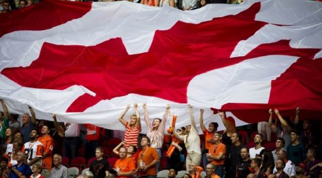 A Canadian flag is passed along fans during the B.C Lions home opener against the Saskatchewan Roughriders over during their CFL football game in Vancouver.