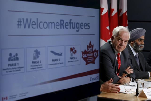 Canada's Immigration Minister John McCallum (L) and Defence Minister Harjit Sajjan attend a news conference in Ottawa