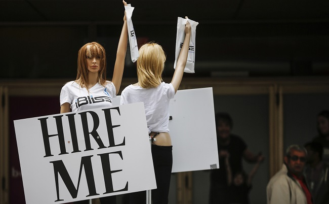 "Motorized mannequins hold signs that read ""Hire Me"" in Toronto"