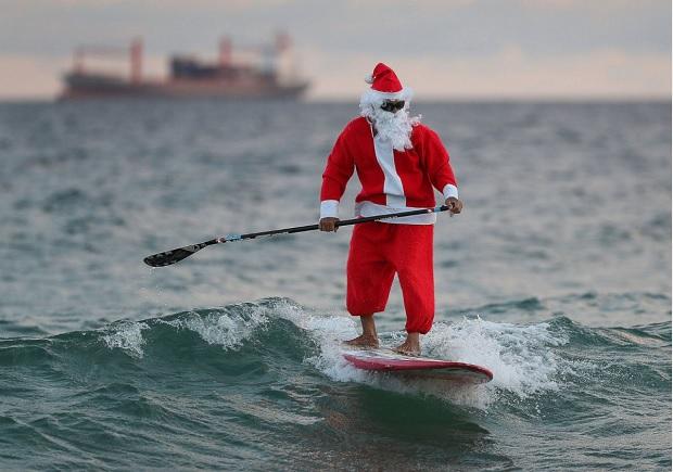 بابانوئل در تلاش برای حفظ تعادل روی paddle board در شهر فورت لادردیل در فلوریدا