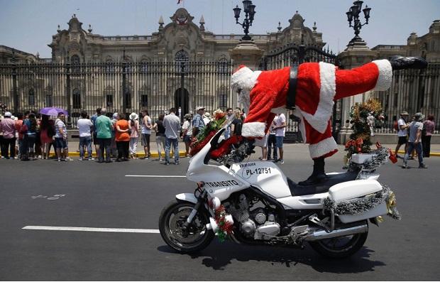 مارکو چیرا افسر پلیس شهر لیما در پرو با لباس بابانوئل در حال شیرین کاری روی موتورسیکلت