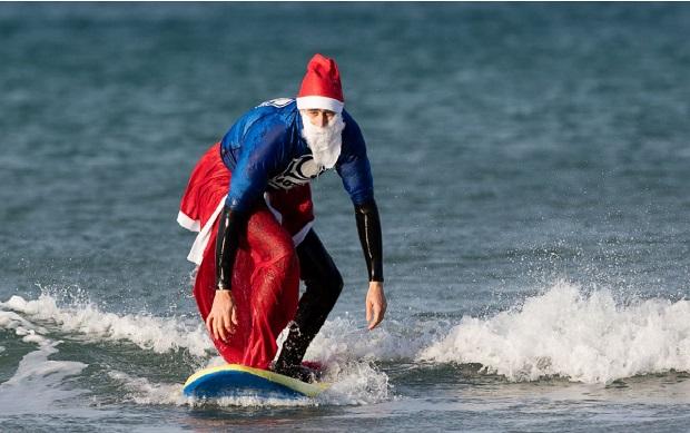یکی از شرکت کنندگان مسابقه موج سواری بابانوئل ها در شهر کورن وال انگلستان