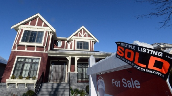 a-real-estate-sold-sign-is-shown-outside-a-house-in-vancouver