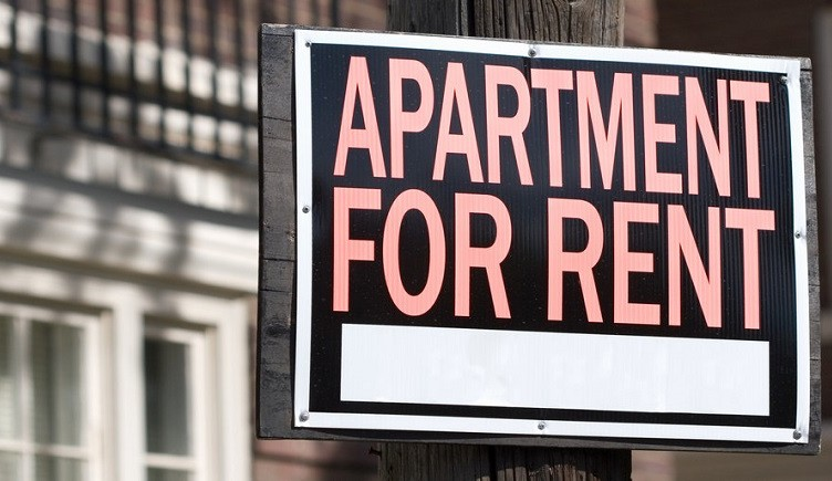 apartment for rent sign in an urban setting